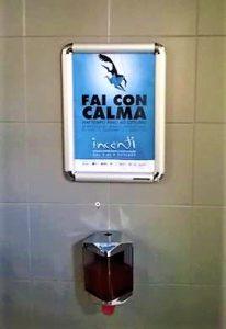 """""""Toilet ADV - Nei bagni, una locandina posizionata all'interno di una cornice messa all'altezza degli occhi"""""""